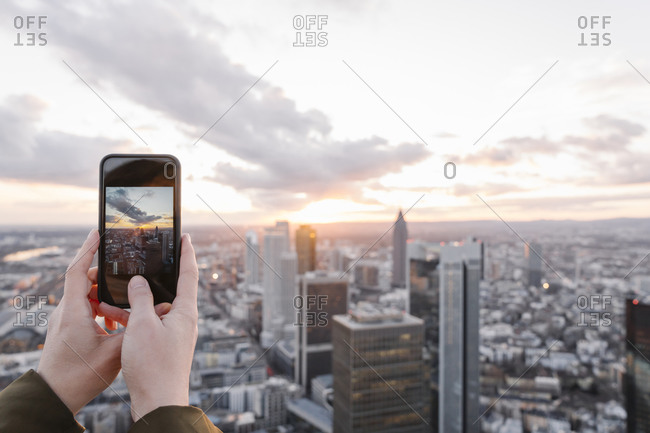 Germany- Hesse- Frankfurt- Hands of woman taking smart phone photos of city downtown at sunset