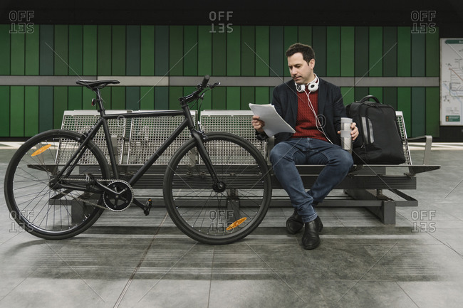 Businessman with bicycle reading documents while sitting at subway station platform- Frankfurt- Germany