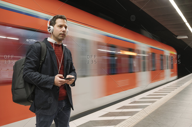 Businessman listening music through mobile phone while standing on platform against subway train
