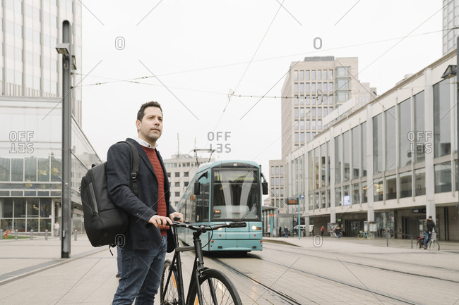 Entrepreneur with bicycle standing against cable car in city- Frankfurt- Germany