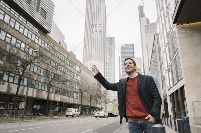 Smiling mid adult businessman hailing taxi while standing on sidewalk in city- Frankfurt- Germany
