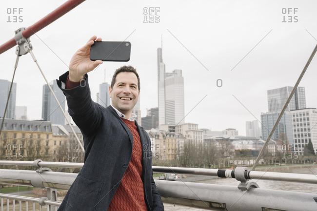 Smiling businessman taking selfie on smart phone while standing on bridge over river- Frankfurt- Germany