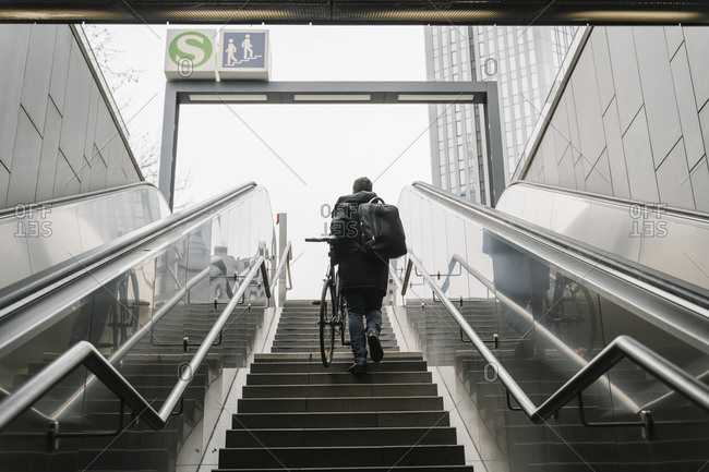 Businessman with bicycle walking on staircase while moving out of subway station in city