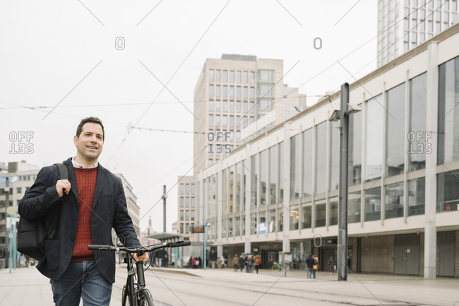 Smiling entrepreneur looking away while walking with bicycle on road in Frankfurt- Germany
