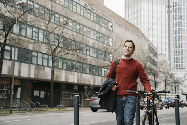 Smiling businessman looking away while walking with bicycle by road in Frankfurt- Germany
