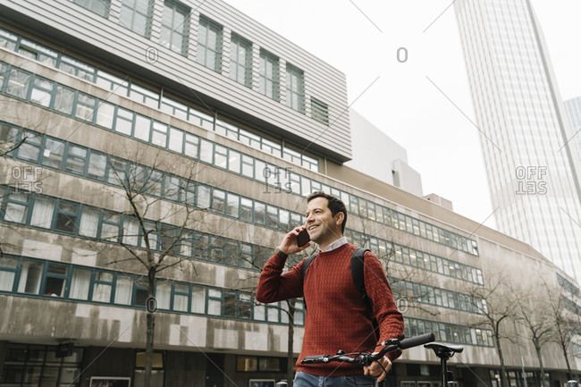Smiling businessman with bicycle talking on smart phone while walking against buildings in city- Frankfurt- Germany