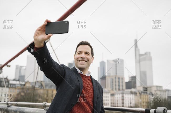 Smiling entrepreneur taking selfie on mobile phone while standing on bridge- Frankfurt- Germany