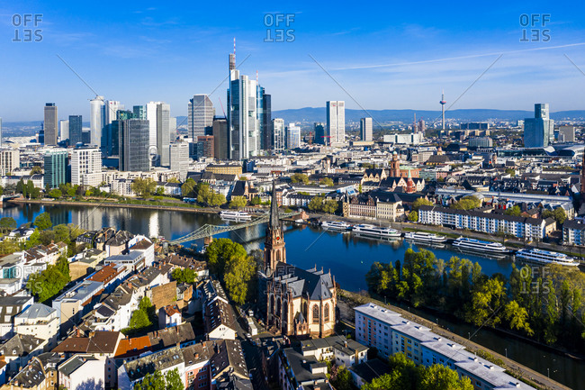 April 16, 2020: Germany- Hesse- Frankfurt- Helicopter view of riverside city with downtown skyscrapers in background