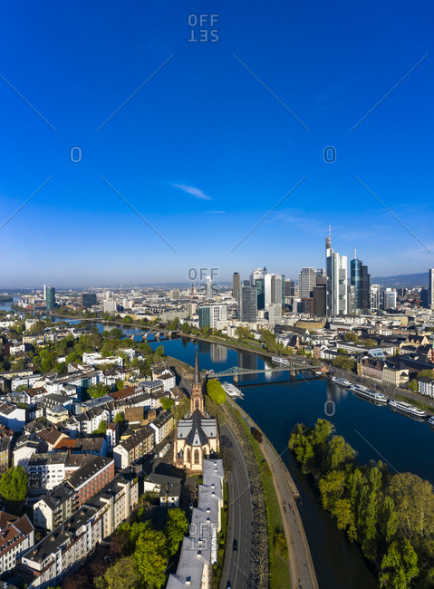 April 16, 2020: Germany- Hesse- Frankfurt- Helicopter view of clear blue sky over riverside city with downtown skyscrapers in background