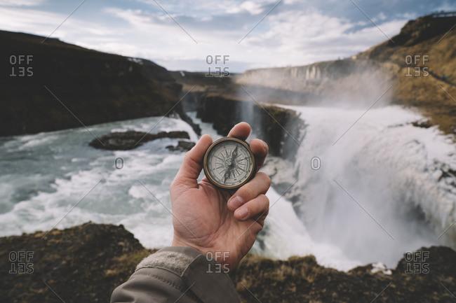 Iceland- Hand of person holdingnavigational compassagainst splashingGullfosswaterfall