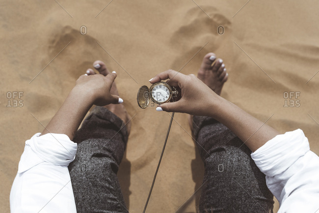 Woman's hand holding old pocket watch- Merzouga desert- Morocco