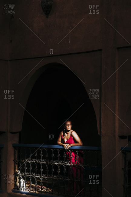 Portrait of young woman leaning on railing looking at distance Morocco