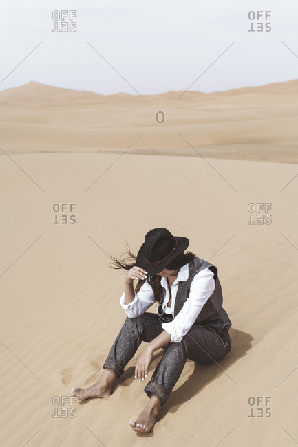 Fashionable young woman sitting barefoot on dune- Merzouga desert- Morocco