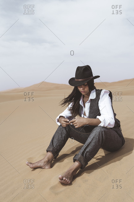 Fashionable young woman sitting barefoot on dune looking at pocket watch- Merzouga desert- Morocco