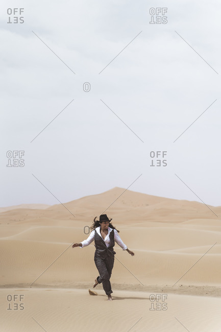 Fashionable young woman dancing barefoot on sand dune- Merzouga desert- Morocco