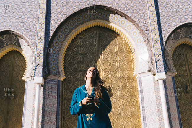 Young woman standing in front of traditional acritude wearing Moroccan robe- Morocco