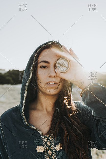 Portrait of young woman covering eye with compass- Morocco