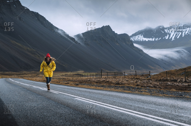 Iceland- Woman in yellow coat running along remote Icelandic highway