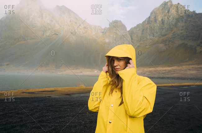 Portrait of woman wearing yellow coat standing at beach in Hvalnes Nature Reserve Beach- Iceland