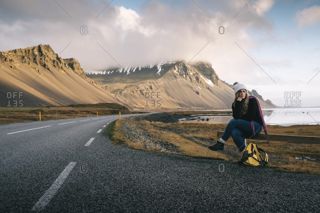 Woman with backpack sitting on railing while waiting at roadside against mountains in Iceland