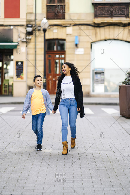 Happy mother walking hand in hand on the street with her son