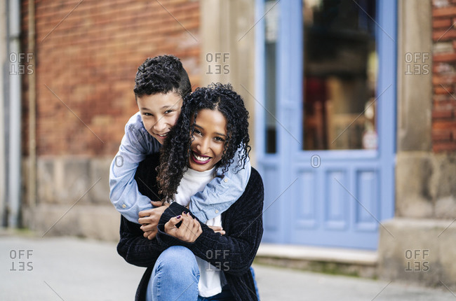 Portrait of happy mother and her son on the street