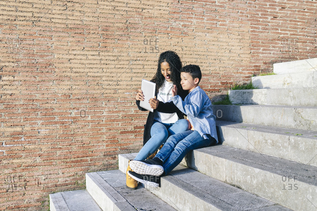 Mother and son sitting together on stairs taking selfie with digital tablet