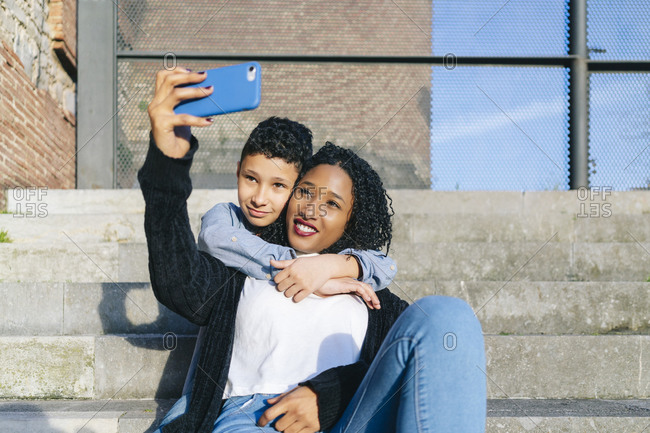 Mother and son sitting together on steps taking selfie with smartphone