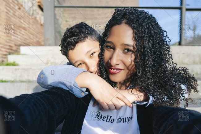 Portrait of happy mother and son sitting together on steps taking selfie