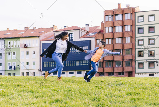 Happy mother and son running hand in hand on a meadow