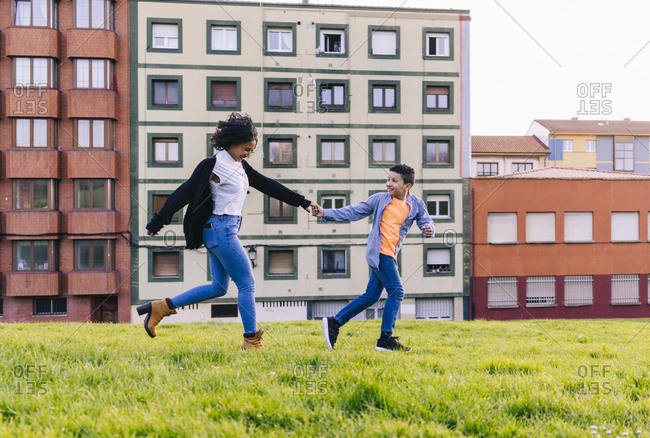 Mother and son running hand in hand on a meadow having fun