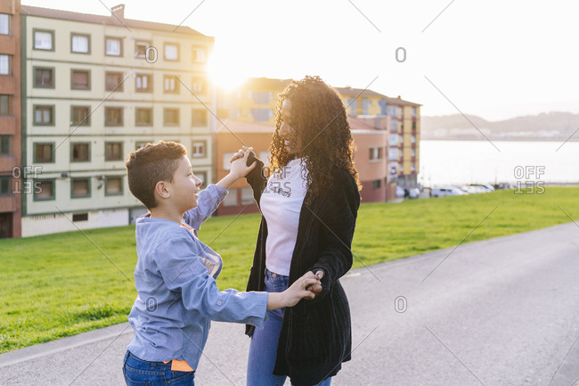 Happy young mother hand in hand with her son at evening twilight
