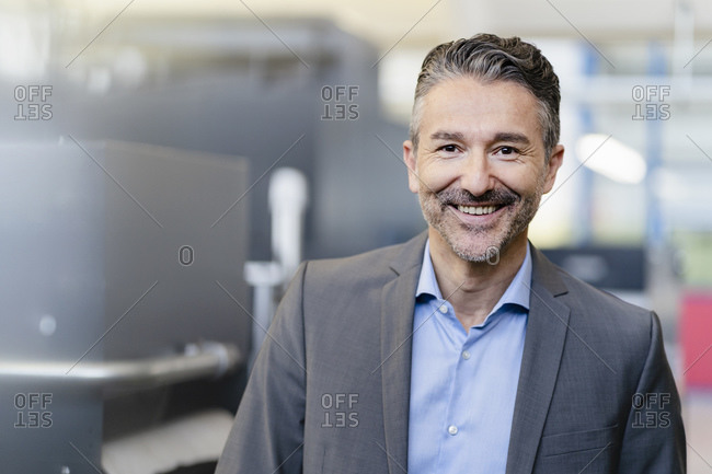 Portrait of successful businessman in shop floor of company- smiling