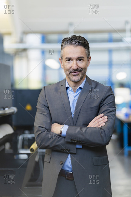 Portrait of successful businessman in shop floor of company- with arms crossed