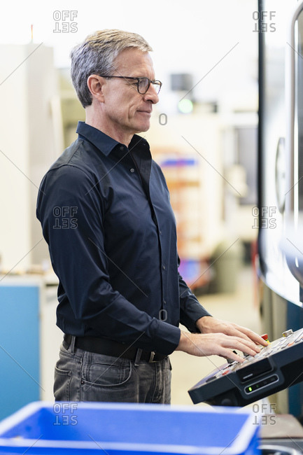 Mature man working on shop floor of industrial company