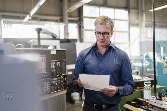 Senior employee checking production plans