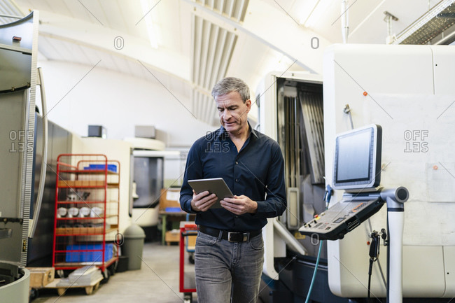 Mature man working on production floor of factory- using digital tablet