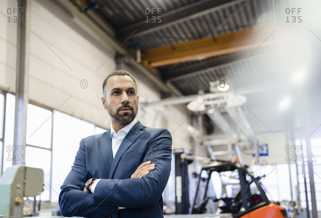 Portrait of a confident businessman in a factory looking around