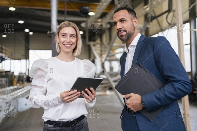 Businessman and smiling young woman with tablet in a factory