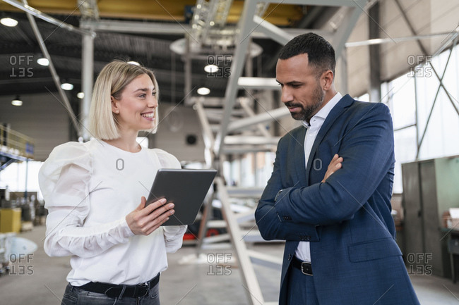 Businessman and young woman with tablet talking in a factory