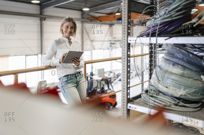 Portrait of smiling young woman using tablet in a factory