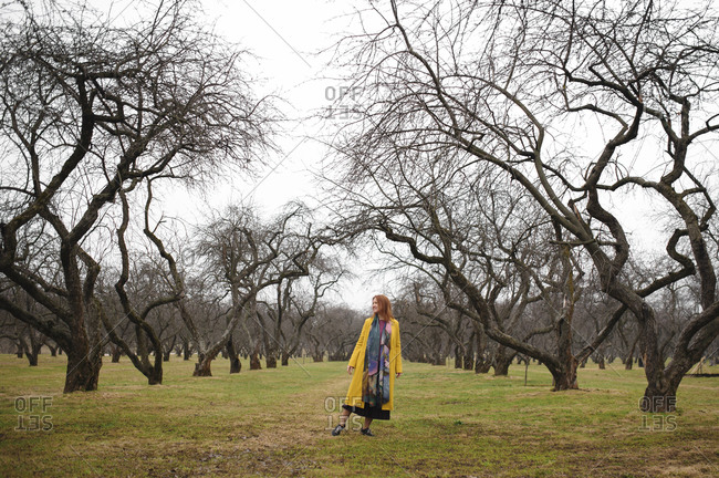 Full length of woman in yellow coat standing amidst bare trees at park- Russia- Moscow