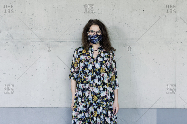 Woman wearing homemade mask in front of a wall