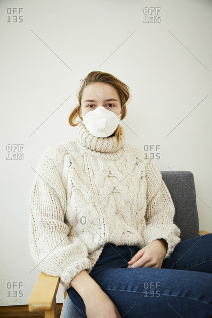 Portrait of blond woman wearing FFP2 mask at home