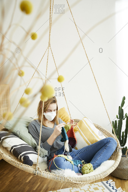 Blond woman wearing FFP2 mask and knitting sitting in hanging chair at home