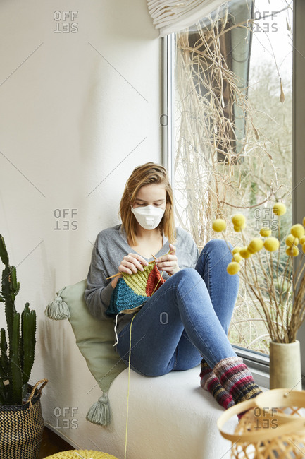 Blond woman wearing FFP2 mask and knitting at home