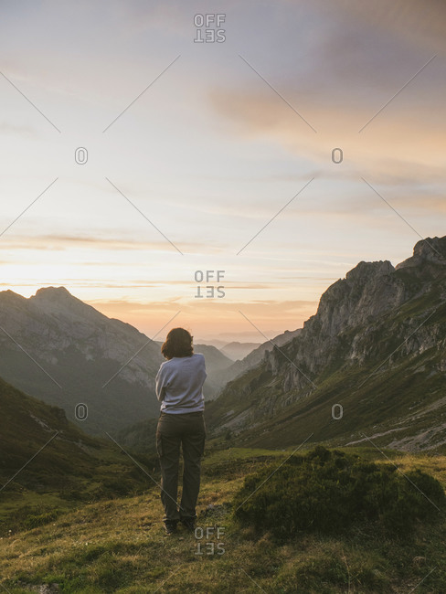 Spain- Cantabria- Young woman admiring valley in Picos de Europa at moody dawn