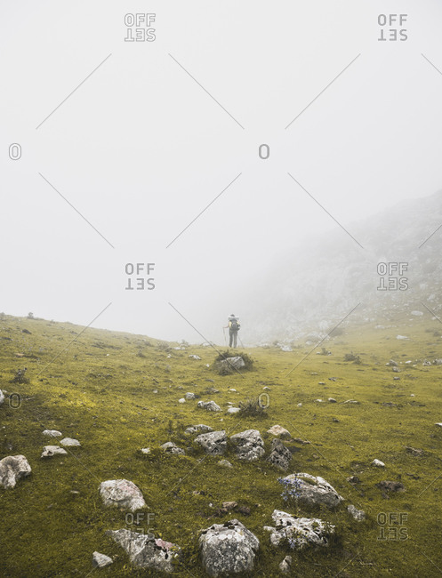 Spain- Cantabria- Female backpacker hiking in Picos de Europa during foggy weather