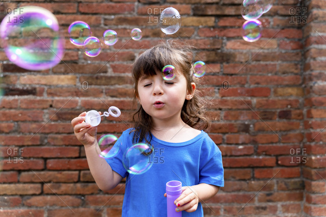 Portrait of little girl with eyes closed blowing soap bubbles in front of brick wall