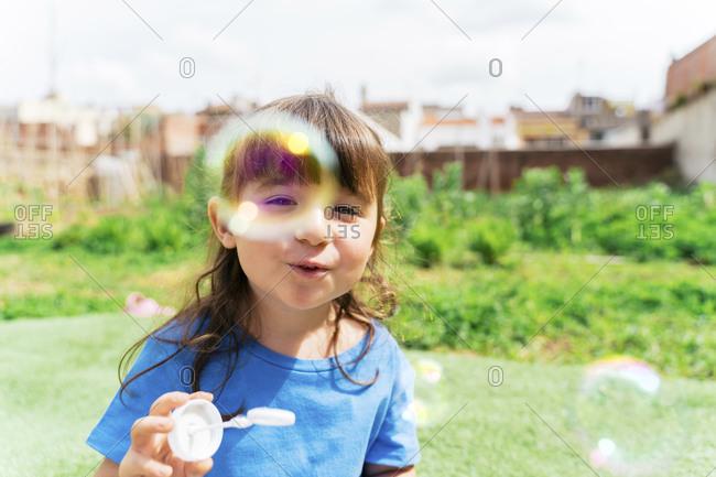 Portrait of happy little girl blowing soap bubbles in a park